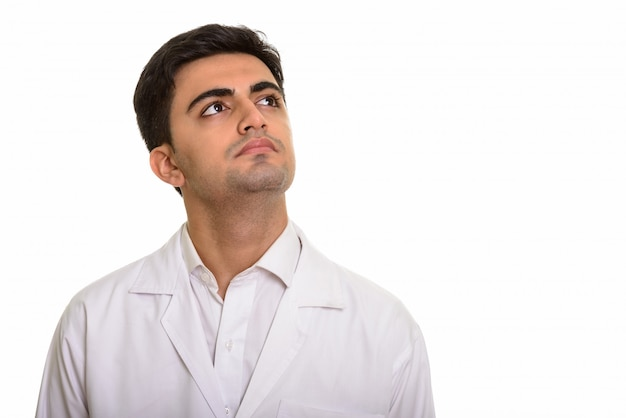 Jeune bel homme médecin pensant et levant