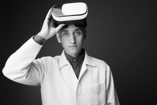 Jeune bel homme médecin portant un casque de réalité virtuelle contre le mur gris. noir et blanc