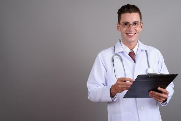 Jeune bel homme médecin portant des lunettes sur gris