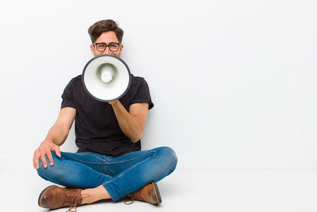 Jeune bel homme avec un mégaphone, assis sur le sol, assis sur le sol dans une salle blanche