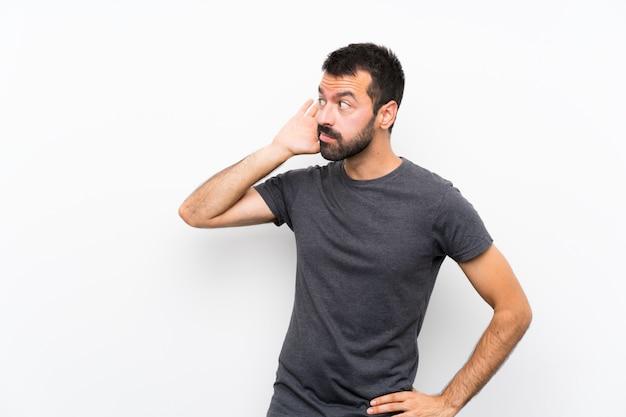 Jeune bel homme sur un mur blanc isolé, écouter quelque chose en mettant la main sur l'oreille