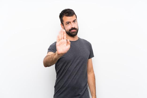 Jeune bel homme sur un mur blanc isolé, faisant un geste d'arrêt
