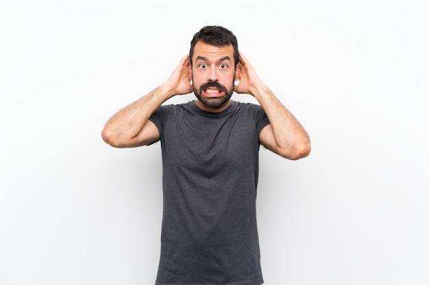 Jeune bel homme sur un mur blanc isolé frustré et prend les mains sur la tête