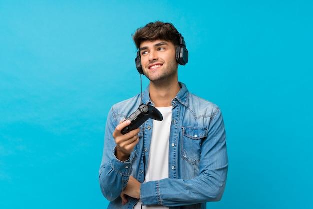 Jeune bel homme sur mur bleu isolé, jouant aux jeux vidéo