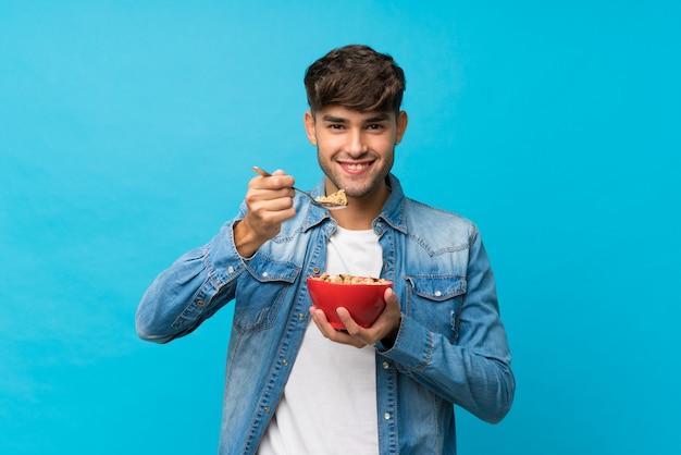 Jeune bel homme sur mur bleu isolé, tenant un bol de céréales