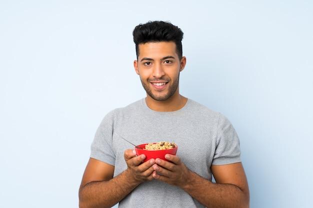 Jeune bel homme sur mur isolé tenant un bol de céréales