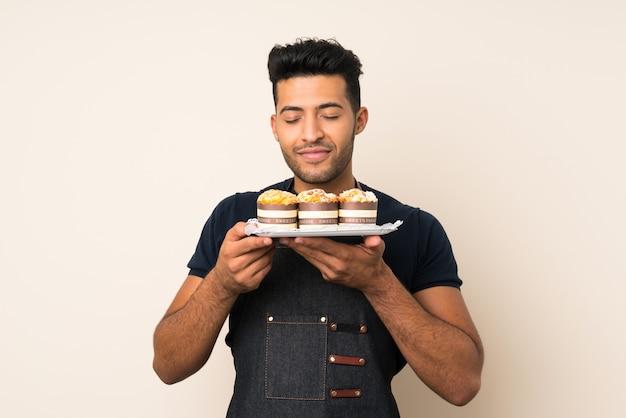 Jeune bel homme sur mur isolé, tenant des mini gâteaux en appréciant leur odeur