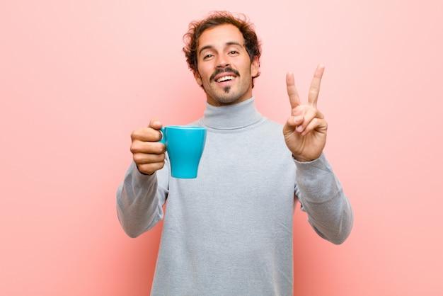 Jeune bel homme avec un mur plat tasse de café rose