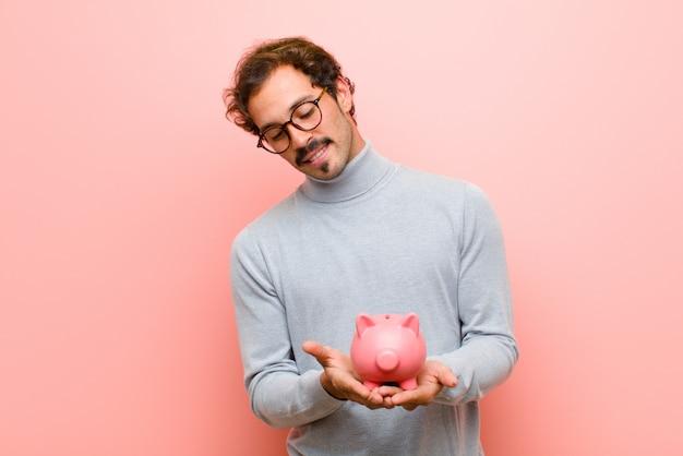 Jeune bel homme avec un mur plat tirelire rose