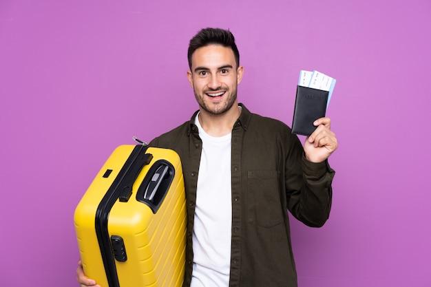 Jeune bel homme sur mur violet isolé en vacances avec valise et passeport