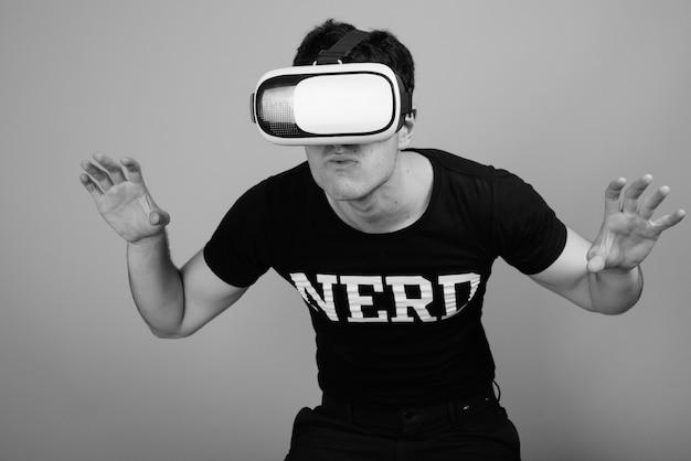 Jeune bel homme nerd persan avec des lunettes contre un mur gris en noir et blanc