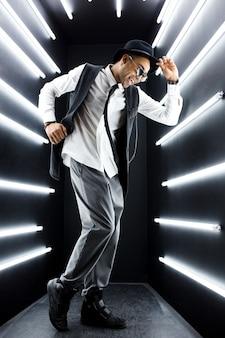 Jeune bel homme noir hipster souriant en costume de style rétro vintage dansant le hip hop en discothèque, s'amusant