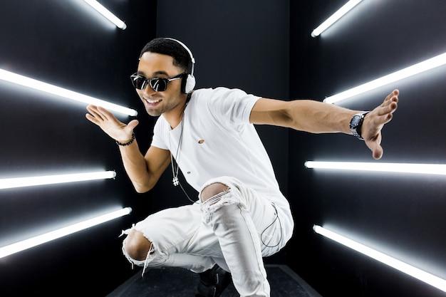 Jeune bel homme noir hipster souriant en tenue blanche écoutant de la musique sur des écouteurs et dansant dans un style hip hop dans une discothèque disco, s'amusant