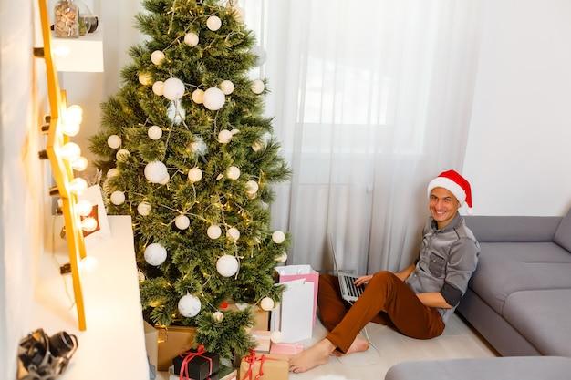 Jeune bel homme avec ordinateur portable dans le cadre de noël à la maison.