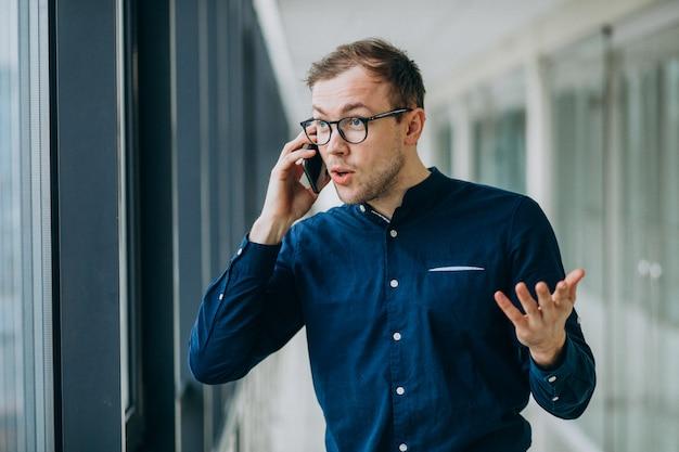 Jeune bel homme parlant au téléphone au bureau