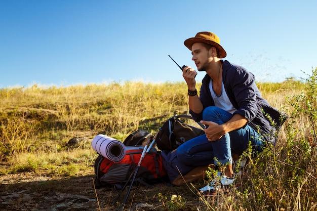 Jeune bel homme parler sur radio talkie-walkie, profiter de la vue du canyon