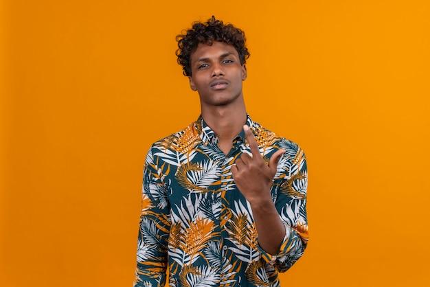 Un jeune bel homme à la peau sombre avec des cheveux bouclés en chemise imprimée de feuilles avec une expression confiante en levant la main