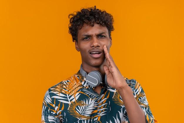 Un jeune bel homme à la peau sombre avec des cheveux bouclés en chemise imprimée de feuilles avec visage agressif appelant quelqu'un tenant la main sur le visage