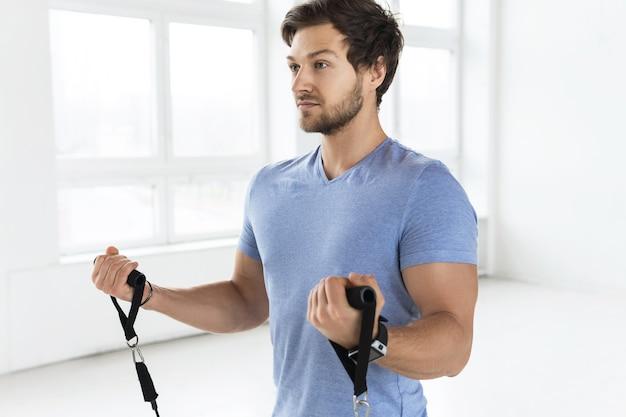 Jeune bel homme pendant l'entraînement avec des élastiques de résistance dans la salle de gym. exercice de flexion des biceps.