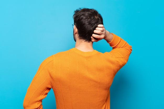 Jeune bel homme pensant ou doutant, se grattant la tête, se sentant perplexe et confus, vue arrière ou arrière