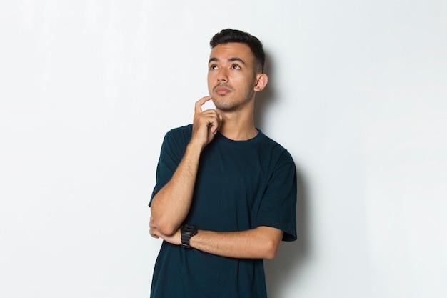 Jeune bel homme pensant isolé sur fond blanc