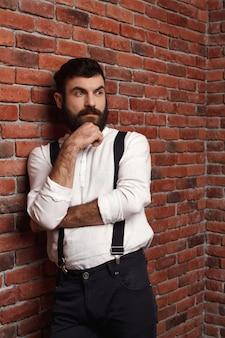 Jeune bel homme pensant posant sur le mur de briques.