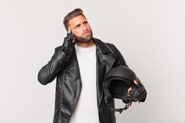 Jeune bel homme pensant, se sentant dubitatif et confus. concept de casque de moto