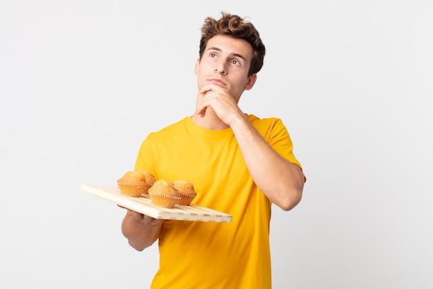 Jeune bel homme pensant, se sentant dubitatif et confus tenant un plateau à muffins