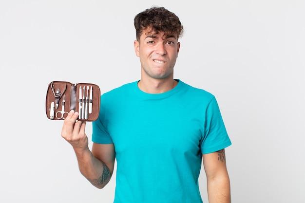 Jeune bel homme à la perplexité et à la confusion et tenant un étui à outils à ongles