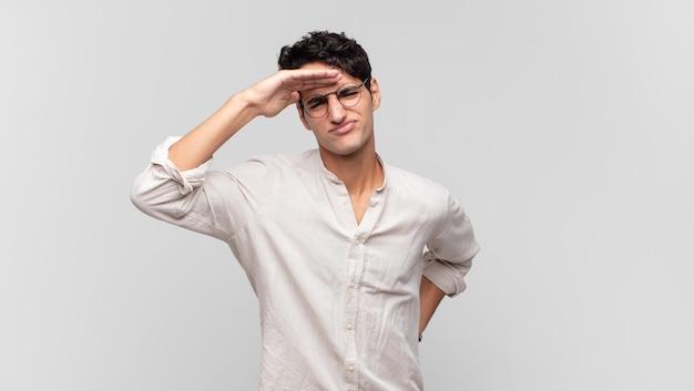 Jeune bel homme à la perplexité et étonné, avec la main sur le front à la recherche de loin, regarder ou chercher