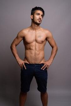 Jeune bel homme persan torse nu sur fond gris