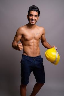 Jeune bel homme persan travailleur de la construction torse nu