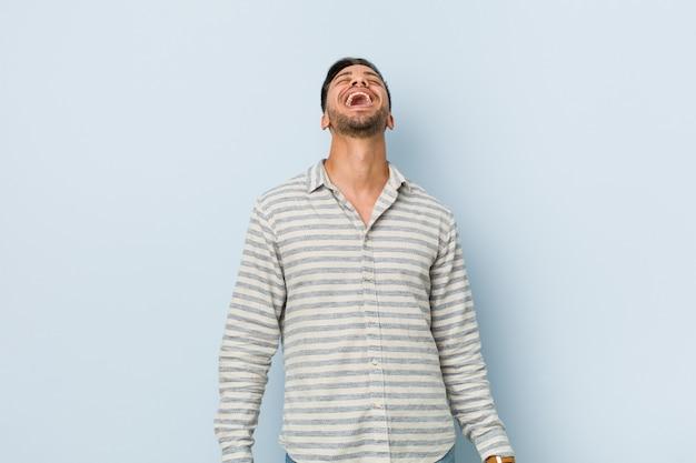 Jeune bel homme philippin détendu et heureux en riant, cou tendu montrant les dents.