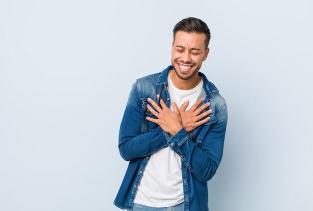 Jeune bel homme philippin rire gardant les mains sur le coeur, concept de bonheur.