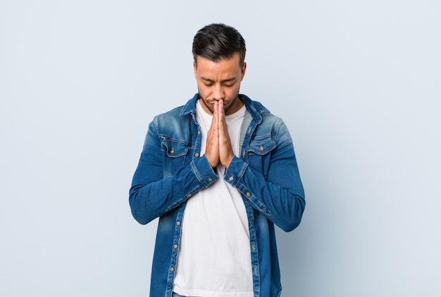 Jeune bel homme philippin tenant par la main dans la prière près de la bouche, se sent confiant.