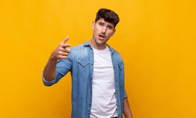 Jeune bel homme pointant la caméra avec une expression agressive en colère ressemblant à un patron furieux et fou