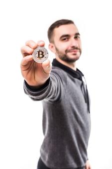 Jeune bel homme a pointé le bitcoin doré sur appareil photo isolé sur blanc