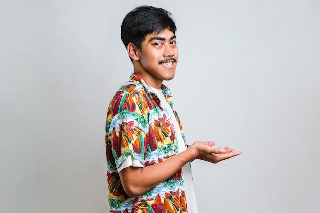 Jeune bel homme portant une chemise décontractée sur fond blanc isolé pointant de côté avec les mains ouvertes les paumes montrant l'espace de copie, présentant une publicité souriante excitée heureuse