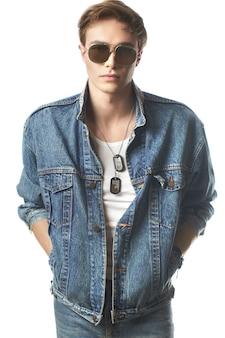 Jeune bel homme portant des jeans jaket en studio