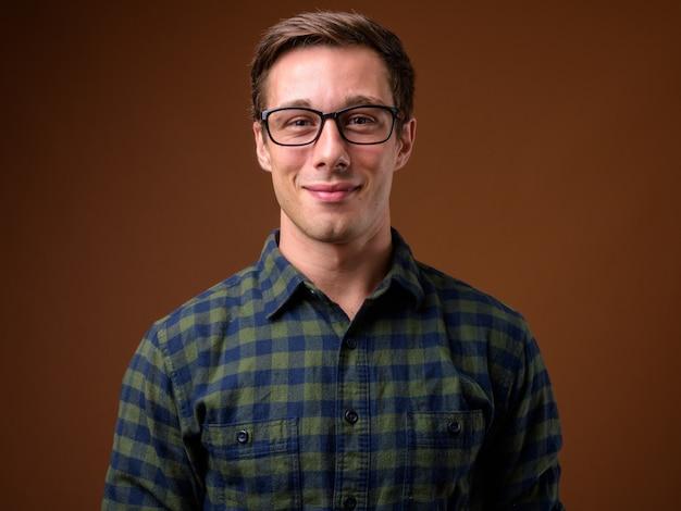 Jeune bel homme portant des lunettes sur fond marron