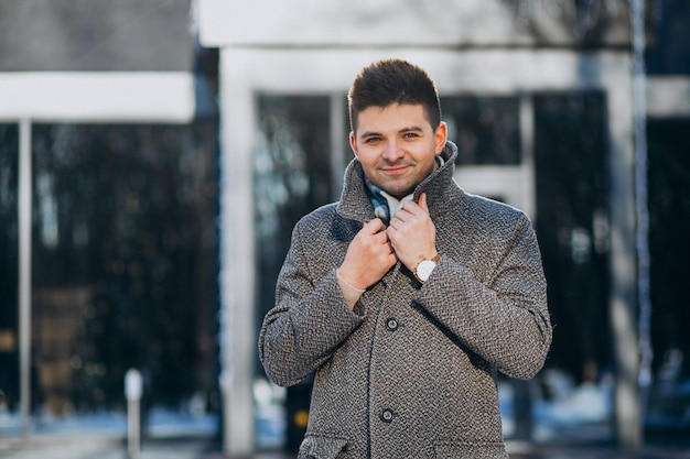 Jeune bel homme portant un manteau à l'extérieur dans le parc