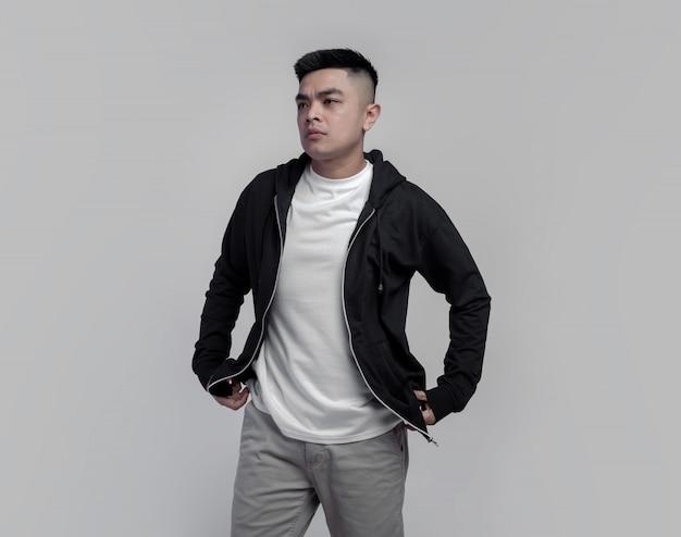 Jeune bel homme portant un sweat à capuche noir et un t-shirt blanc isolé sur fond