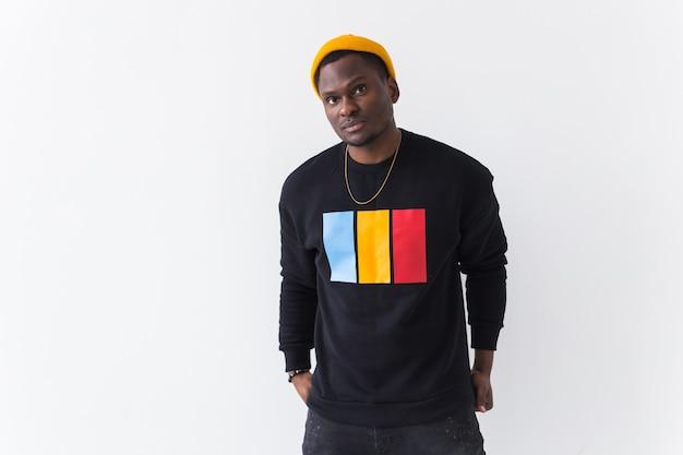 Jeune bel homme portant un sweat-shirt contre le mur blanc