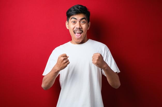 Jeune bel homme portant un t-shirt blanc debout sur fond rouge isolé très heureux et excité faisant le geste du vainqueur avec les bras levés, souriant et criant pour le succès. notion de célébration