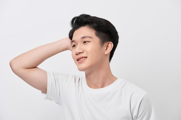 Jeune bel homme portant un t-shirt blanc sur fond isolé sourire confiant toucher les cheveux avec le geste de la main