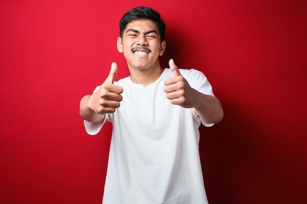 Jeune bel homme portant un t-shirt blanc sur fond rouge approuvant un geste positif avec la main, le pouce levé souriant et heureux du succès. geste du vainqueur.