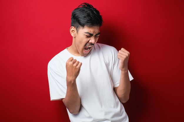 Jeune bel homme portant un t-shirt décontracté debout sur fond rouge isolé très heureux et excité faisant le geste du vainqueur avec les bras levés, souriant et criant pour le succès. notion de célébration