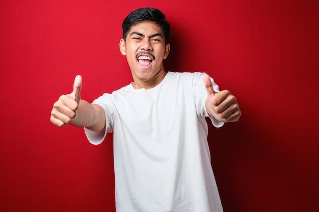 Jeune bel homme portant un t-shirt décontracté sur fond rouge approuvant un geste positif avec la main, le pouce levé souriant et heureux de réussir. geste du vainqueur.