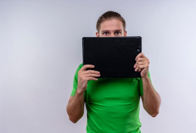 Jeune bel homme portant un t-shirt vert tenant un porte-documents se cachant derrière debout sur fond blanc