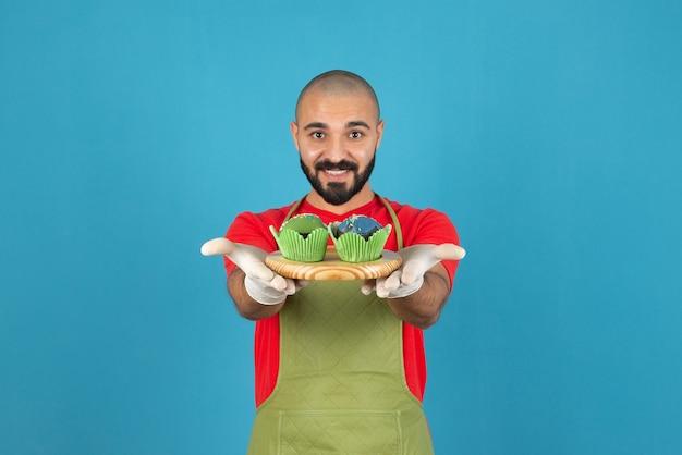 Jeune bel homme portant un tablier tenant des cupcakes contre le mur bleu.